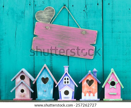 Blank pink wood sign with heart and row of birdhouses hanging on antique teal blue wooden background