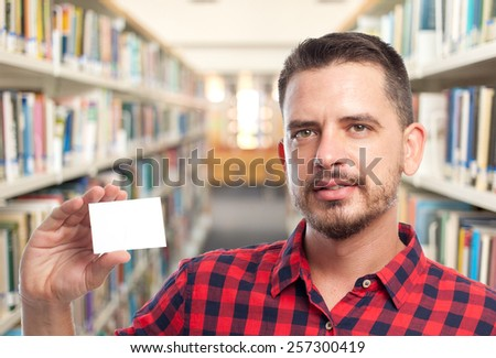 Man with red squares shirt. He is holding a white card. Over library background #257300419