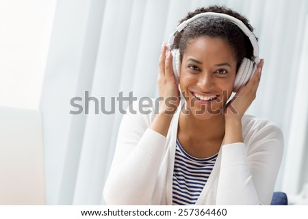 Woman in headphones sitting at desk in office #257364460