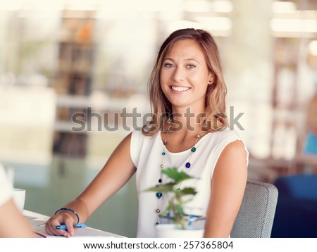 Happy and confident young woman in an office #257365804