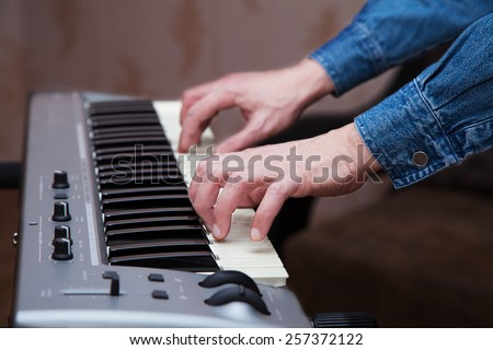 hands of the musician on the keyboard synthesizer Royalty-Free Stock Photo #257372122