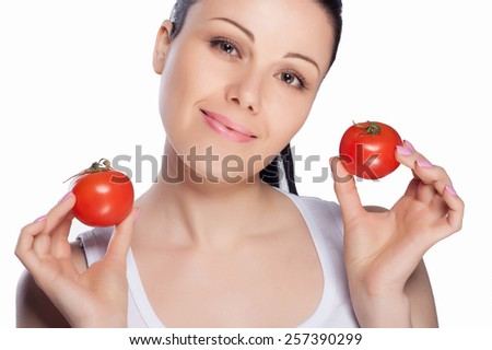 Beautiful close-up portrait of young woman with tomato. Healthy food and vegetables concept. Skin care and beauty. Vitamins and minerals. #257390299