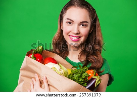 young smiling woman holding a bag full of healthy food. shopping #257391079