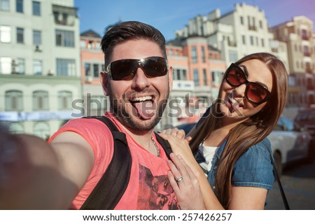 young couple taking fun photos on the phone, show language