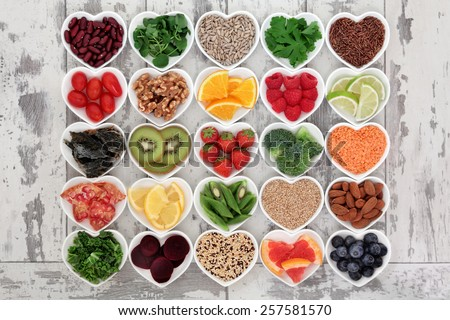 Diet detox super food & immune boosting food collection in heart shaped porcelain bowls over rustic wood background. Foods high in antioxidants, anthocaynins, omega 3, protein, vitamins & minerals.   Royalty-Free Stock Photo #257581570