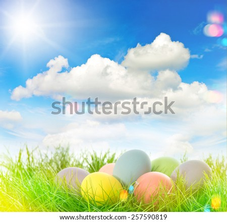 Easter eggs decoration in green grass. Beautiful sunny blue sky. Retro style toned picture with light leaks and lens flares