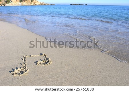 Musical note in the sand on the beach with sea