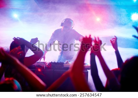 Charismatic disc jockey at the turntable Royalty-Free Stock Photo #257634547