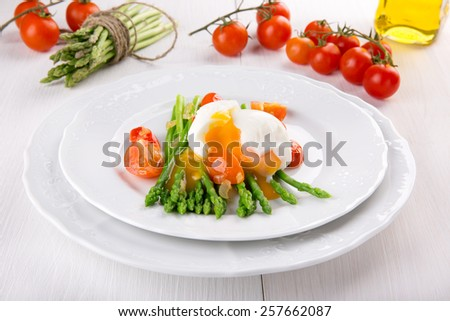Green asparagus stems with soft-boiled egg, tomato and sauce. #257662087