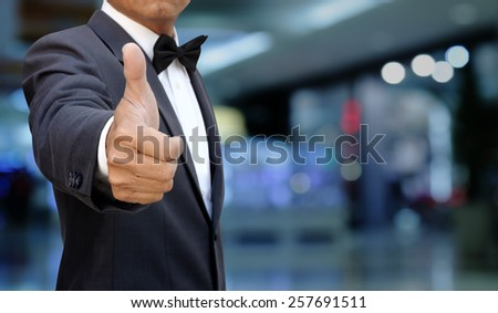 businessman thumbs up in blur building #257691511