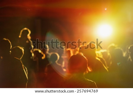 crowd at a concert in a red light noise added #257694769