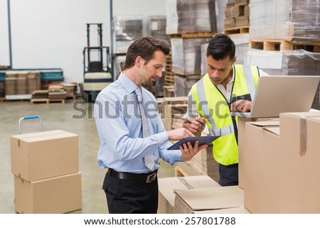 Warehouse worker and manager working together in a large warehouse #257801788