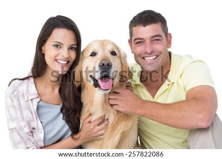 Portrait of happy loving couple stroking dog over white background #257822086