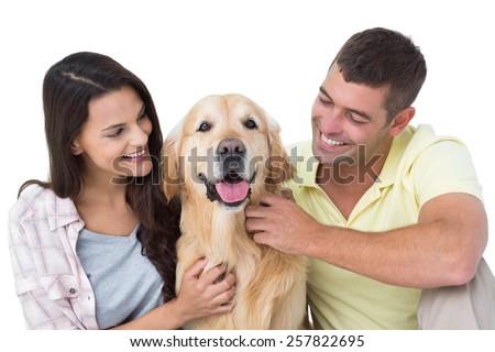 Happy loving couple stroking dog over white background #257822695