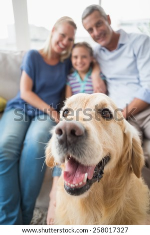 Golden Retriever with happy family in background at home #258017327