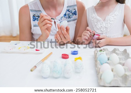 Mother and daughter painting easter eggs at home in the living room #258052721