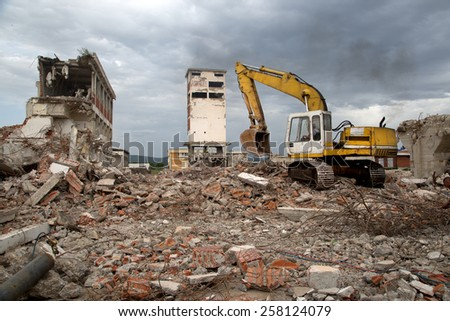 Bulldozer Removes the Debris From Demolition of Old Derelict Buildings on the Construction Site #258124079