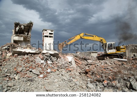 Bulldozer Removes the Debris From Demolition of Old Derelict Buildings on the Construction Site #258124082