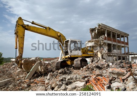 Bulldozer Removes the Debris From Demolition of Old Derelict Buildings on the Construction Site #258124091