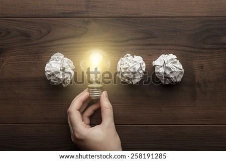 new idea concept with crumpled office paper, female hand holding light bulb Royalty-Free Stock Photo #258191285