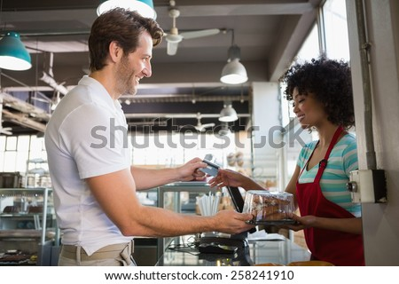 Smiling customer paying by credit card at the bakery