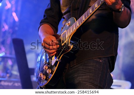 artist Guitarist hand play  electricity guitar on concert stage with blue light, Practicing in playing . song entertainment and music instrument. #258415694