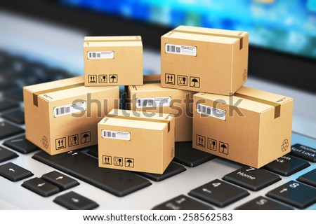 Shipping, delivery and logistics technology business industrial concept: macro view of heap of stacked corrugated cardboard package boxes on computer PC laptop notebook keyboard with selective focus #258562583