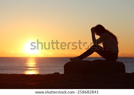 Sad woman silhouette worried on the beach at sunset with the sun in the background Royalty-Free Stock Photo #258682841