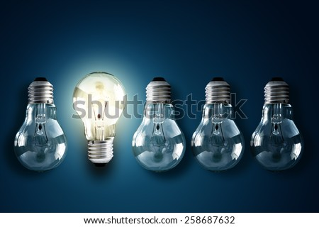 Illuminated light bulb in a row of dim ones concept for creativity, innovation and solution Royalty-Free Stock Photo #258687632