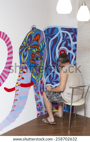 The artist draws a picture sitting on a chair with an elephant on the living room wall.