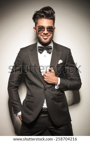 Portrait of a young business man smiling at the camera while fixing his jacket and holding one hand in his pocket. #258704216