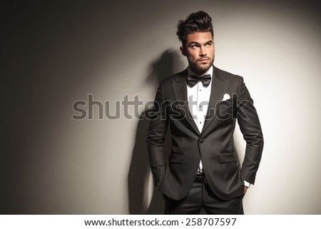 Picture of a young handsome business man looking up while holding both hands in his pocket. #258707597