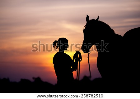 The girl near to a horse standing in front of a beautiful sunset. Silhouette of a woman and a horse. Human holding the horse by the rope. #258782510