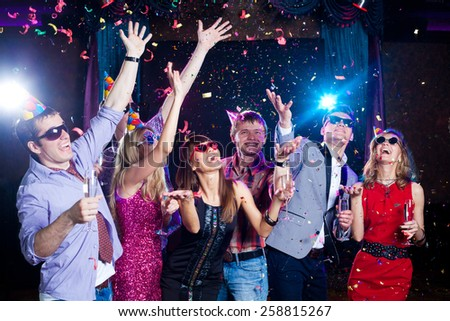 Cheerful young people showered with confetti on a club party. #258815267