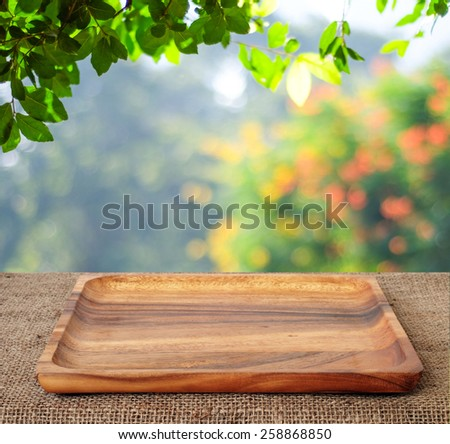 Food background, Empty wooden plate, tray for kitchen product display on table over blur green tree nature garden outdoor with bokeh light in spring and summer background, mockup, template, banner #258868850