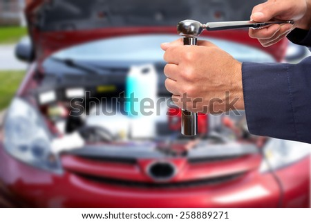 Hand of car mechanic with wrench. Auto repair garage. #258889271