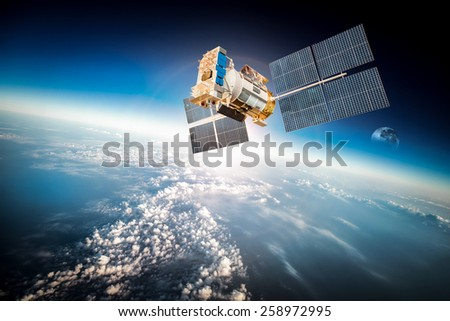 Space satellite orbiting the earth. Elements of this image furnished by NASA. Royalty-Free Stock Photo #258972995