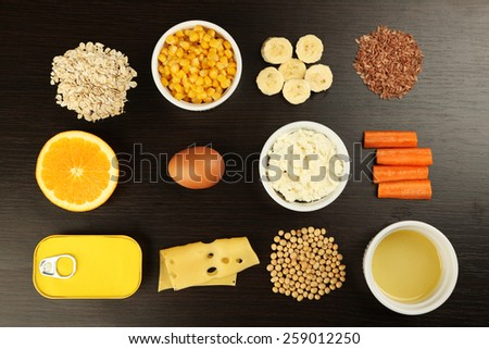 Various food products containing vitamins on wooden background #259012250