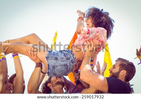 Happy hipster woman crowd surfing at a music festival Royalty-Free Stock Photo #259017932