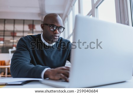 Young businessman working on his laptop in office. Young african executive sitting at his desk surfing internet on laptop computer. #259040684