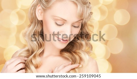 beauty, people, hair care and health concept - beautiful young woman face with long wavy hair over beige lights background #259109045