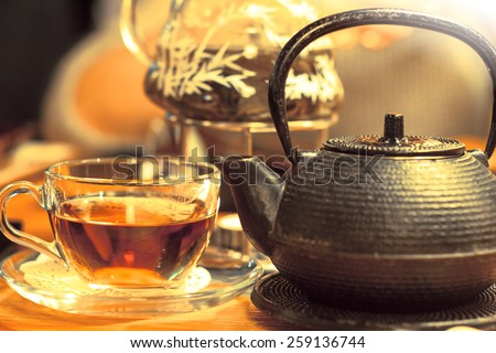 a healthy cup of hot tea and the kettle on the side, a vintage looking very fine bronze kettle or pot