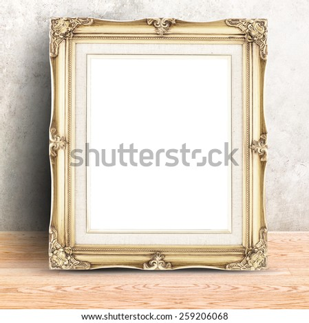 Golden Vintage photo frame at Concrete wall and wooden table,Template mock up for display of product.