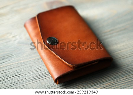 Hand made leather man wallet on wooden background Royalty-Free Stock Photo #259219349