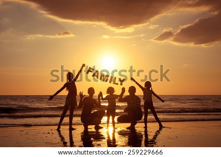 "Happy family standing on the beach at the sunset time. They keep the letters forming the word "" family"". Concept of friendly family. #259229666"
