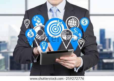 businessman with digital tablet and drawing business icons