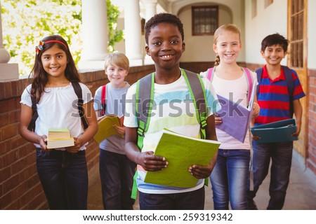 Portrait of smiling little school kids in school corridor Royalty-Free Stock Photo #259319342