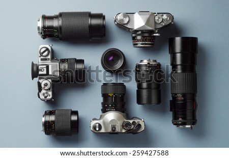 Collection of vintage cameras and camera lens well organized over blue background, top view #259427588