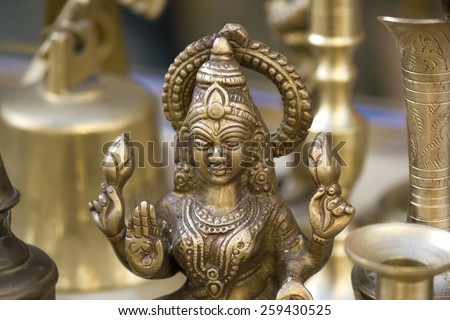 Closeup to a brass figure of the Hindu goddess Lakshmi in a craft fair. Stock photography. #259430525