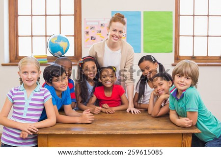 Cute pupils and teacher smiling at camera in classroom at the elementary school #259615085